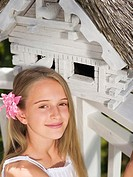 Girl sitting in front of birdhouse, portrait