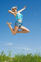 Germany, Bavaria, Young woman jumping in meadow