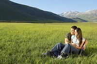 Young couple sitting in mountain field looking at view full length