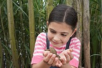 Girl 5_6 holding toad by fence