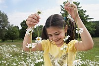 Girl 7_9 holding flowers in meadow