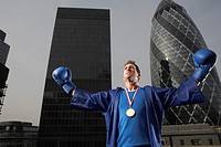 Boxer wearing gold medal standing in front of downtown skyscrapers low angle view London England
