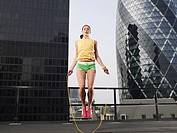 Woman skipping on skipping rope on downtown rooftop low angle view London England