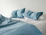 Morning view of an unmade bed with crumpled blue bed linens and no people