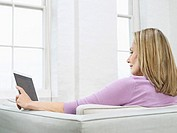 Mid adult woman using laptop on sofa profile