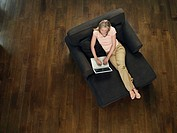 Mid_adult woman sitting on sofa using laptop view from above