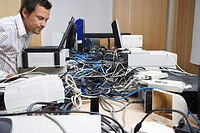 Office worker looking at mess of wires connecting computers and printer in office