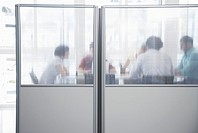 Office workers meeting behind cubicle wall in office