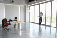 Man using mobile phone leaning against window in empty office building