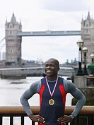 Man standing in front of Tower Bridge wearing medal England London