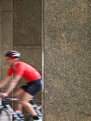 Man cycling between pillars motion blur