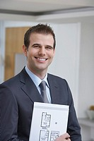Male estate agent holding brochure smiling portrait
