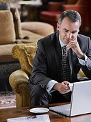 Business man sitting in lobby working on laptop