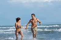 Couple running in surf smiling