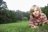 Portrait of boy 7_9 lying in meadow