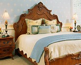 Carved Headboard against Light Blue Wallpaper in Bedroom