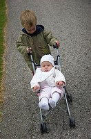 little boy with baby in stroller