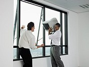 Businessmen Throwing a Computer Monitor out the Window