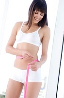 Young smiling woman measuring waist with tape measure
