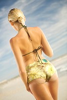 Young woman in bikini standing on beach, rear view