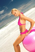 Young smiling woman in pink bikini on the beach, sitting on a large ball
