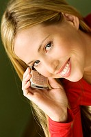 Portrait of a young smiling woman, using mobile phone (thumbnail)
