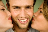 2 young women kissing smiling man