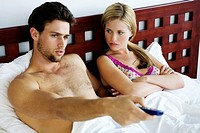 Young couple in bed, watching TV
