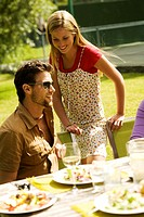 Young smiling couple at garden table