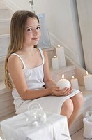 Christmas, little girl sitting indoors, holding a candle, indoors