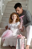 Father and daughter with Christmas presents, girl holding a princess costume, indoors