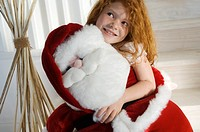 Christmas day, portrait of a little girl holding a cuddly toy Santa Claus, indoors