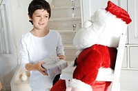 Little boy holding a present, looking at a cuddly toy Santa Claus, indoors