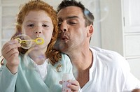Father and daughter making soap bubbles, indoors