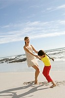 Mother and daughter playing on the beach, outdoors
