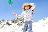 Little girl walking on the beach, holding a landing net, outdoors