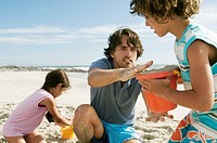 Father and two children playing on the beach, outdoors