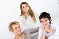 Senior woman and two children smiling for the camera, indoors