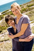 Senior woman and adult daughter embracing, outdoors