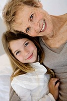 Senior woman and little girl smiling for the camera, indoors (thumbnail)