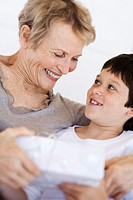 Senior woman giving present to little boy, indoors