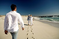 Couple and senior woman walking on beach