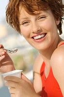 Portrait of a young smiling woman eating yogurt