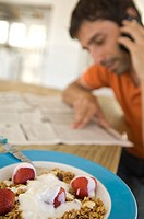 Young man reading newspaper, using mobile phone, strawberries and cereals in foreground