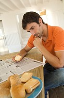 Young man reading newspaper, breads in foreground