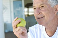 Portrait of a senior man holding an apple