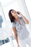 Young woman phoning, holding white balloons