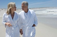Couple in bathrobe walking on the beach