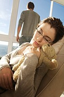 Young woman sleeping with teddy bear, man in background