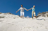 Couple holding hands, running down sand dune
